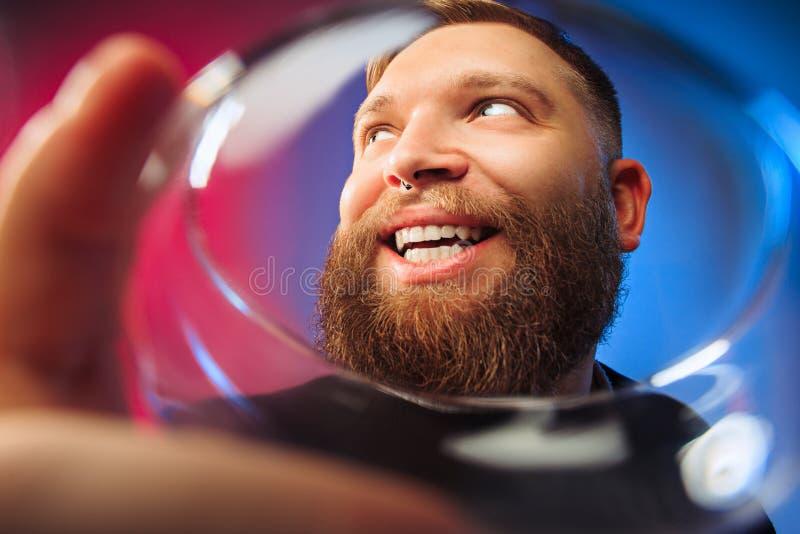 El hombre joven sorprendido que presenta con la copa de vino imagen de archivo libre de regalías