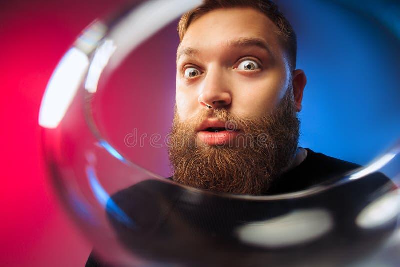 El hombre joven sorprendido que presenta con la copa de vino fotos de archivo