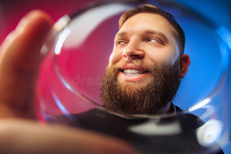 El hombre joven sorprendido que presenta con la copa de vino imagenes de archivo