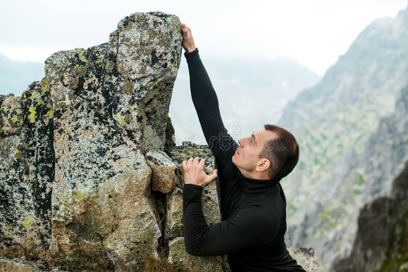 El hombre joven sube la roca contra fondo de la montaña imagenes de archivo