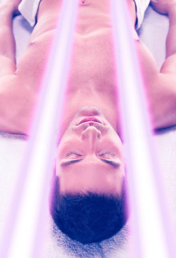 El hombre joven tiene tratamiento de la piel que broncea en solarium moderno fotos de archivo