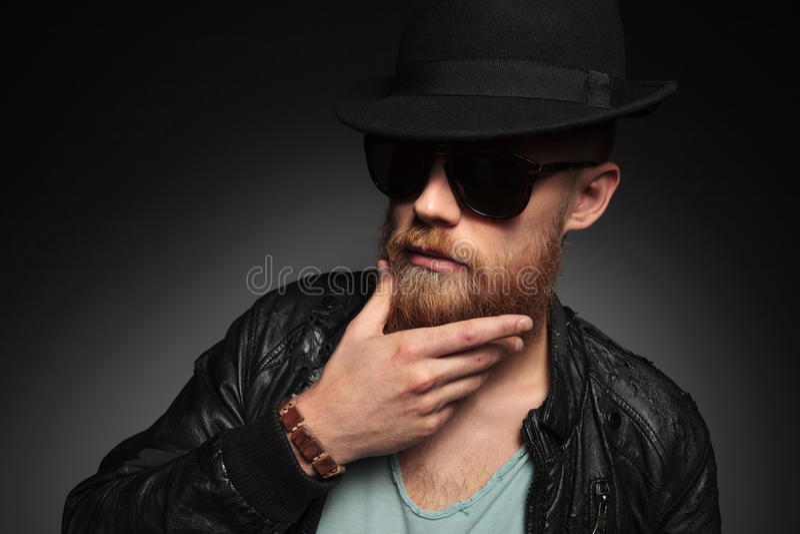 El hombre joven toca su barba imagenes de archivo