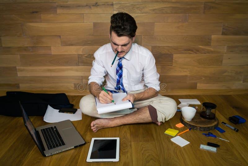 El hombre joven trabaja en casa en ropa divertida y proyecto del comienzo nuevo foto de archivo libre de regalías