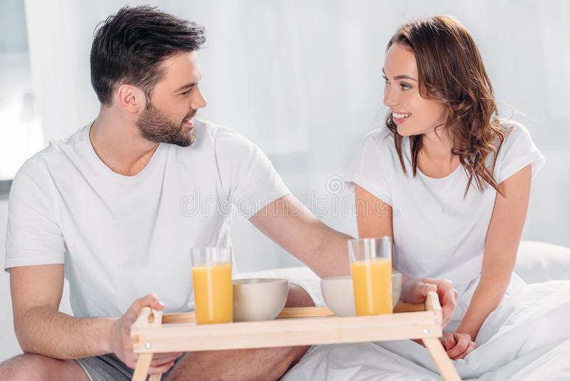 el hombre joven trajo el desayuno en la cama para la novia sonriente imagen de archivo libre de regalías