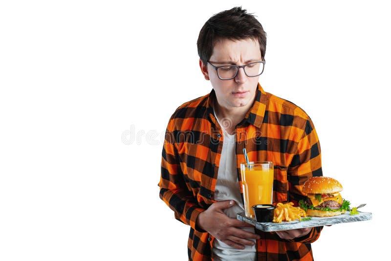 El hombre joven triste de la enfermedad en camisa puso la mano en el abdomen del dolor, estómago-dolor, situación y hamburguesa e fotografía de archivo