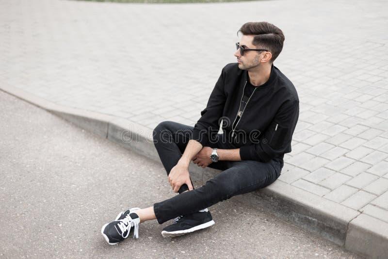 El hombre joven urbano del inconformista en una chaqueta elegante en vaqueros negros en zapatillas de deporte en gafas de sol de  imágenes de archivo libres de regalías