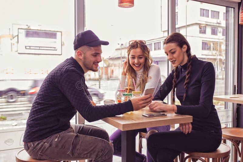 El hombre joven y dos las mujeres que se sientan en la tabla en el café hacen compras imagen de archivo libre de regalías