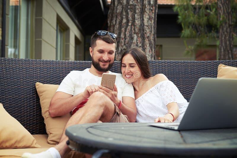 El hombre joven y la mujer en el sofá acogedor están mirando algo en fotos de archivo