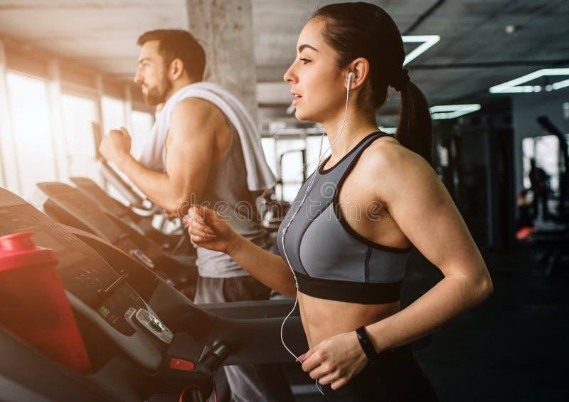 El hombre joven y la mujer están corriendo en la máquina corriente Hacen este ejercicio cada vez que vienen al club de fitness ci imagen de archivo libre de regalías