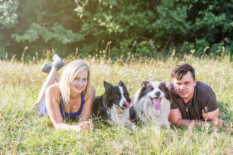 El hombre joven y la mujer están mintiendo en hierba con un par de perros imagenes de archivo