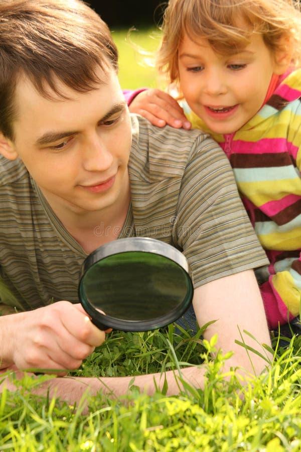 El hombre joven y la niña miran a través de la lupa fotos de archivo