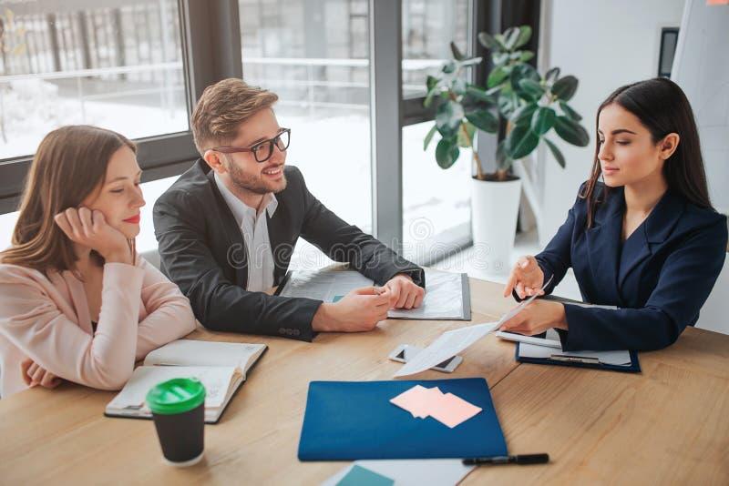El hombre joven y las mujeres se sientan juntos en la tabla en sala de reunión Papel moreno de la demostración a sus colegas Lo m foto de archivo libre de regalías