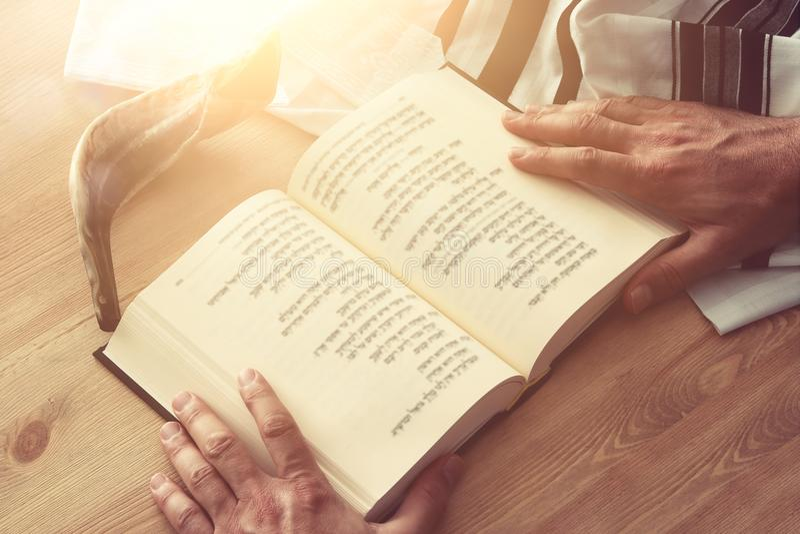 El hombre judío da sostener un libro de oración, rogando, al lado de tallit Símbolos tradicionales judíos Holida judío del Año Nu fotos de archivo
