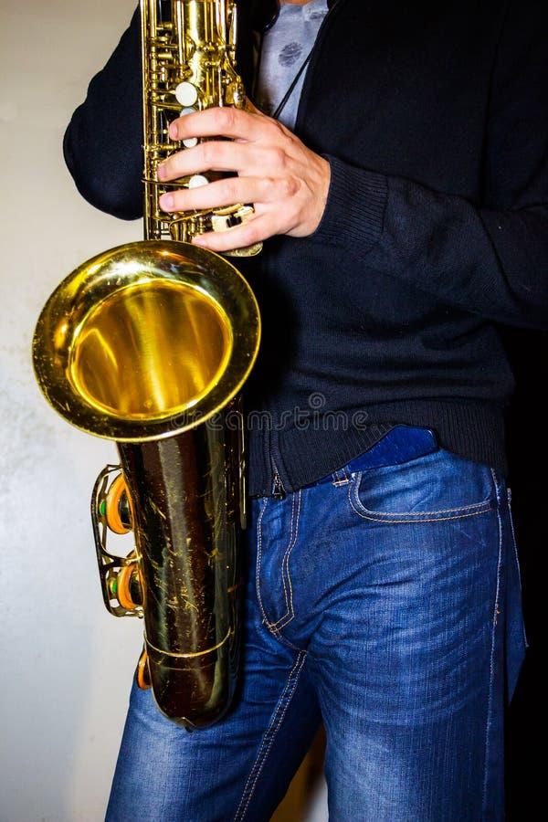 El hombre juega un saxo tenor imagen de archivo