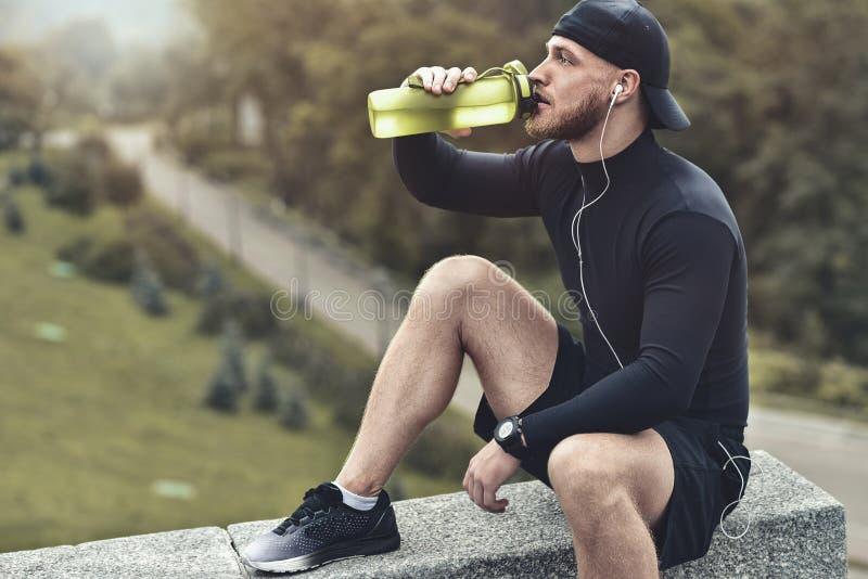 El hombre juguetón barbudo tirado primer toma un resto y bebe un agua después de la sesión del entrenamiento imagen de archivo