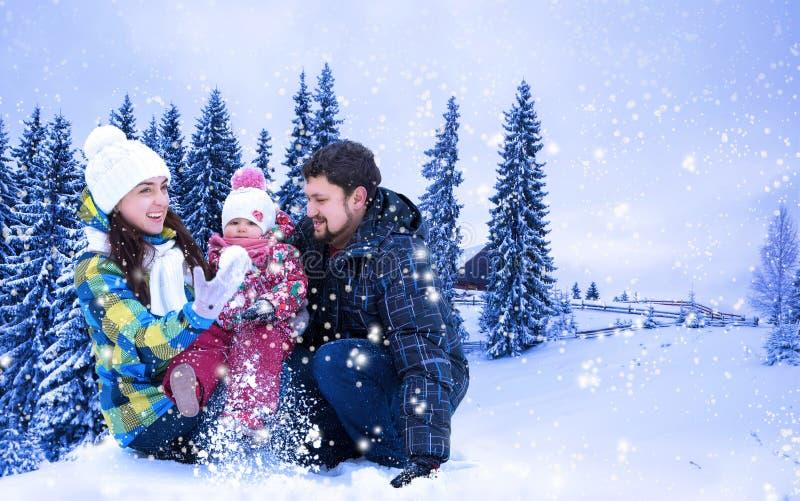 El hombre, la mujer y el niño atractivos en un fondo de una Navidad ajardinan fotos de archivo
