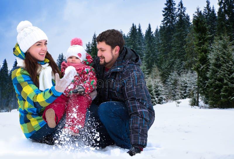 El hombre, la mujer y el niño atractivos en un fondo de una Navidad ajardinan foto de archivo