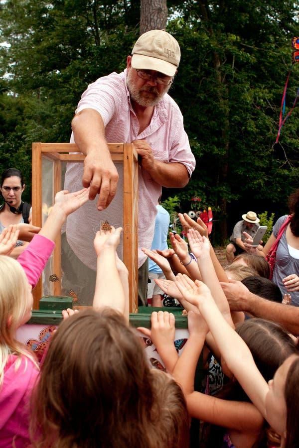 El hombre lanza mariposas a los espectadores jóvenes en el verano Festiv fotografía de archivo