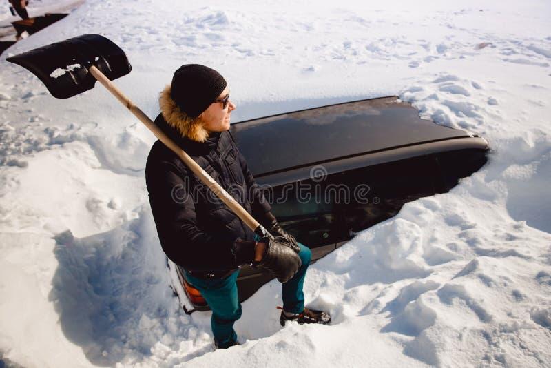 El hombre limpia nieve y limpia la pala del coche de nieve imagen de archivo libre de regalías