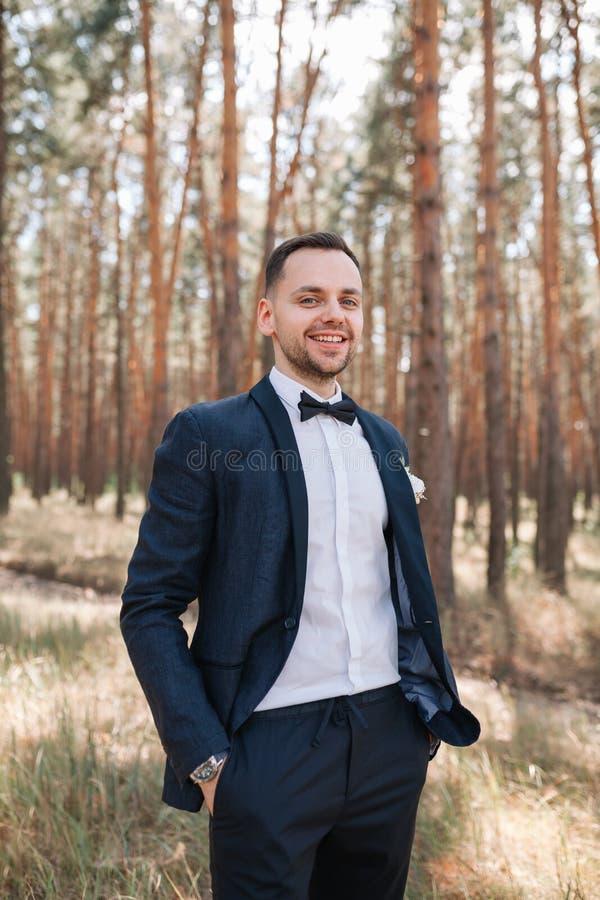 El hombre lindo joven en un traje de negocios blanco de la camisa con una corbata de lazo se está colocando en la naturaleza en e fotografía de archivo