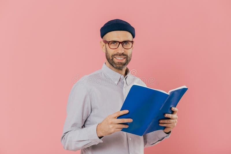 El hombre listo sin afeitar alegre sostiene el libro en frente lee historia emocionante, estudia la literatura científica, lleva  imagen de archivo libre de regalías