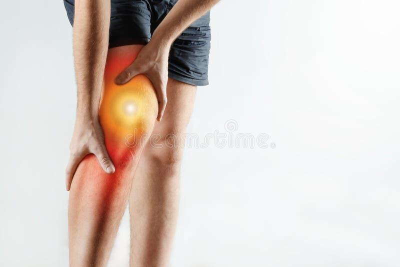 El hombre lleva a cabo sus manos a la rodilla, dolor en la rodilla destacó en rojo, artritis fotografía de archivo