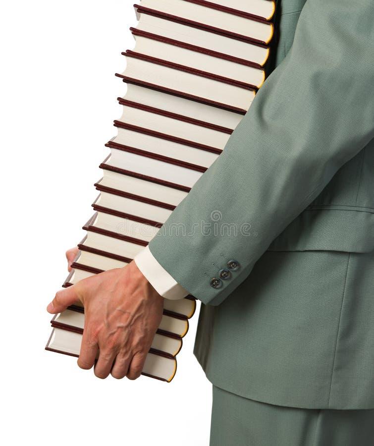 El hombre lleva los libros foto de archivo
