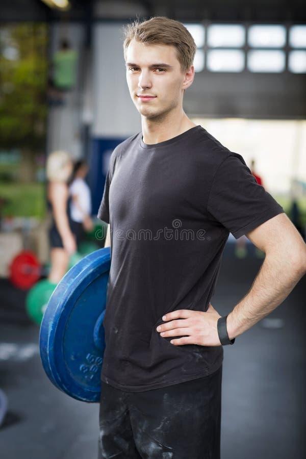 El hombre lleva pesos en el centro del gimnasio de la aptitud imagen de archivo libre de regalías