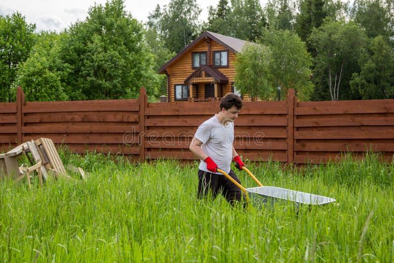 el hombre lleva una carretilla a través del matorral de la hierba imagenes de archivo