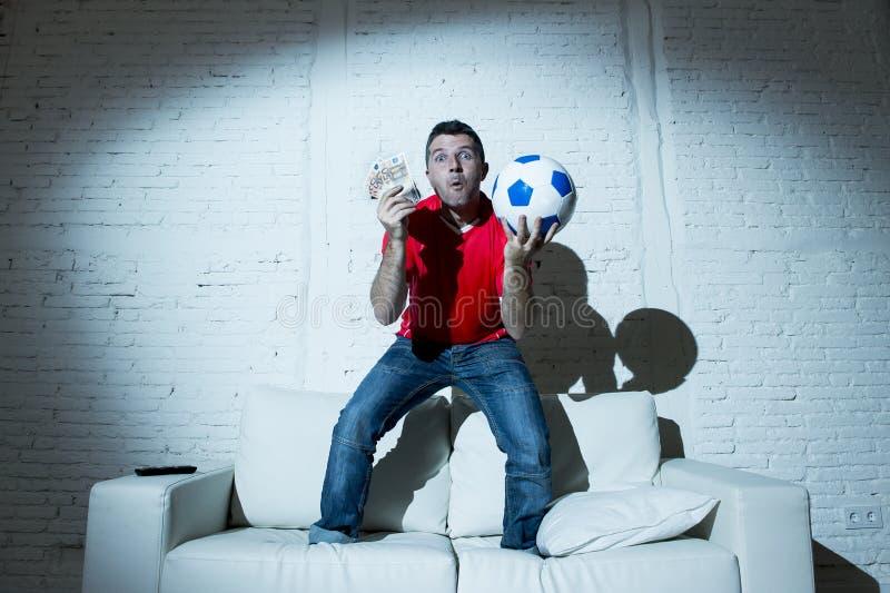 El hombre loco que llevaba a cabo el dinero y el fútbol de observación del balón de fútbol en Internet de la TV en línea apostó e fotos de archivo
