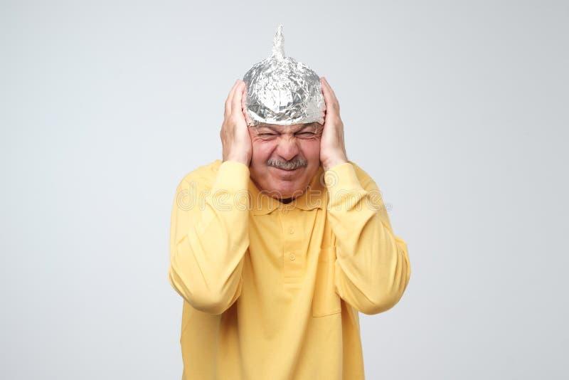 El hombre maduro caucásico en un sombrero de la hoja de lata descontentó la ocultación a partir de vida al aire libre fotos de archivo libres de regalías