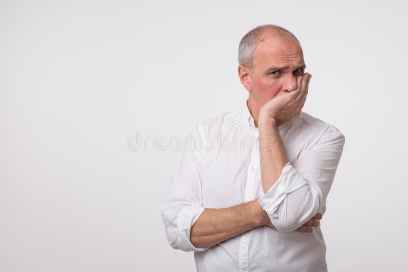 El hombre maduro descontentado en la camisa blanca que cubre su cara con entrega el fondo gris imagen de archivo libre de regalías