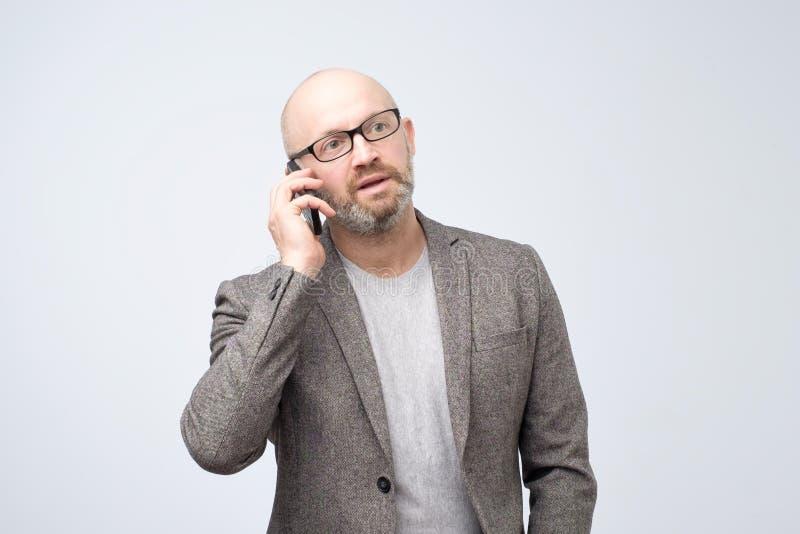 El hombre maduro en traje se está colocando con el teléfono móvil y está hablando con su socio comercial imagen de archivo libre de regalías