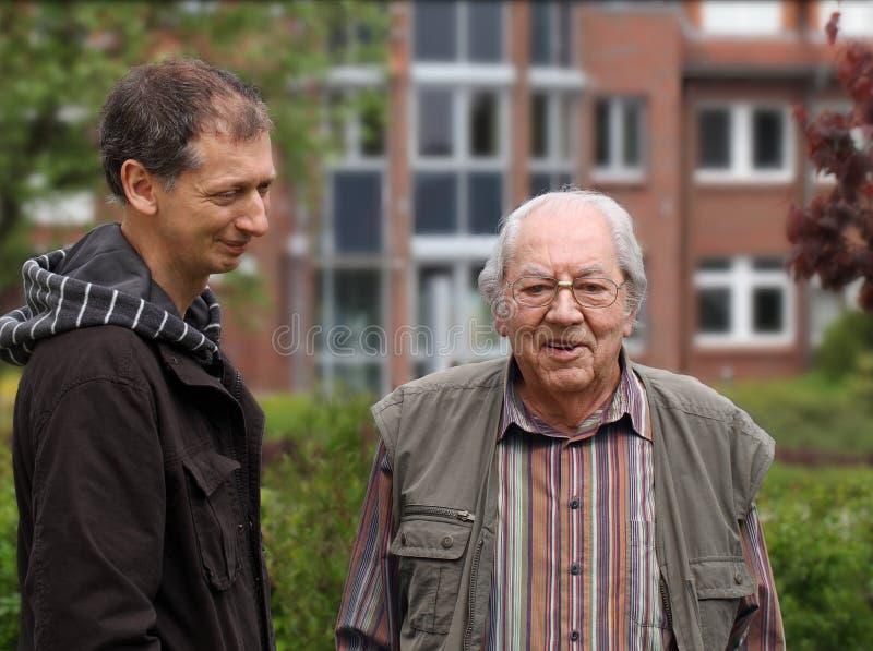 El hombre maduro está visitando al viejo padre imagen de archivo libre de regalías