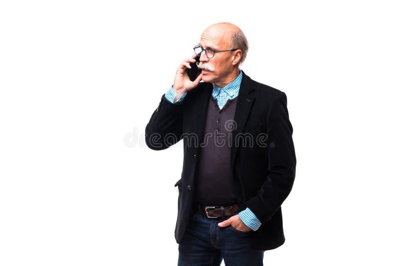 El hombre maduro hermoso está hablando en el teléfono móvil, está mirando la cámara y está sonriendo, aislado en blanco fotografía de archivo libre de regalías