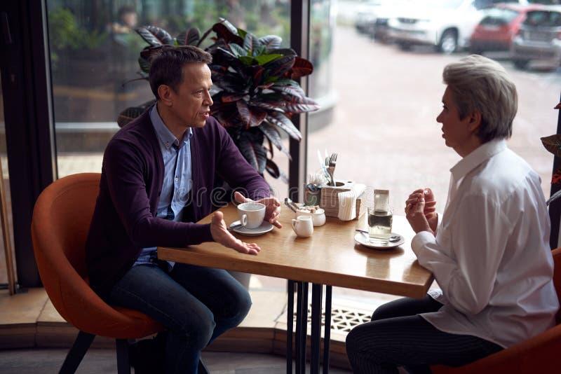 El hombre maduro tiene reunión con la señora en café fotografía de archivo