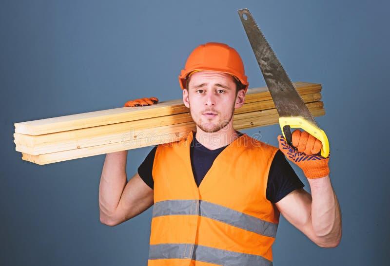 El hombre, manitas en el casco, casco lleva a cabo el handsaw y los haces de madera, fondo gris Concepto del sentido de la orient imagenes de archivo