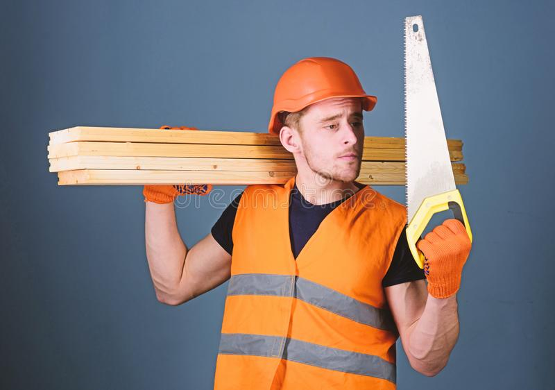 El hombre, manitas en el casco, casco sostiene el handsaw, mira la cuchilla aguda, fondo gris Carpintero, carpintero, trabajador imagenes de archivo