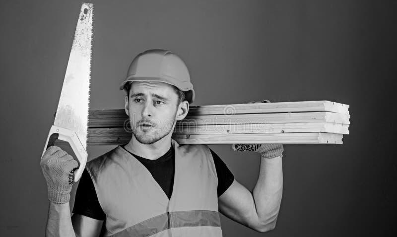 El hombre, manitas en el casco, casco sostiene el handsaw, mira la cuchilla aguda, fondo gris Concepto del carpintero carpintero imagenes de archivo