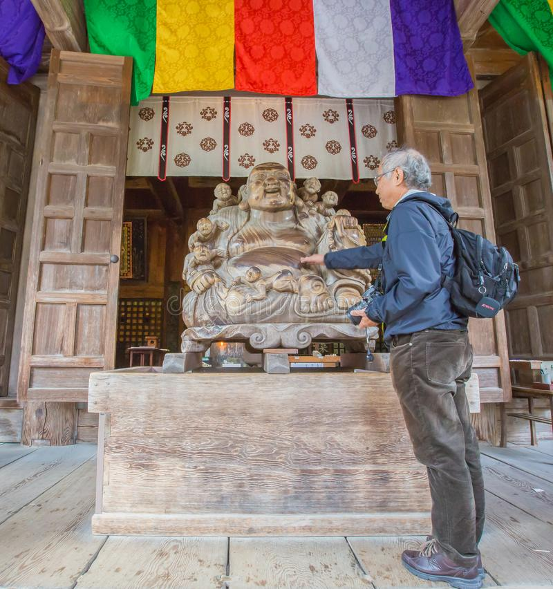 El hombre mayor acarició a su mano en la escultura de Katyayana o de Phra Sangkajai para la buena suerte en el templo de Konponch foto de archivo