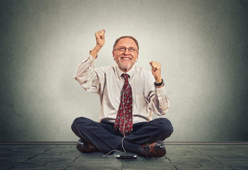 El hombre mayor alegre que guardaba los brazos aumentó para arriba la expresión de positividad mientras que escuchaba la música imágenes de archivo libres de regalías