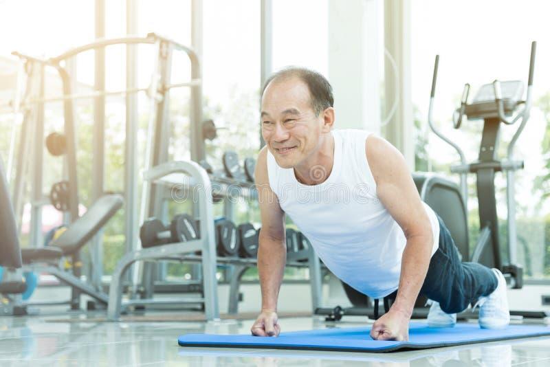 El hombre mayor asiático empuja hacia arriba en el gimnasio imagen de archivo libre de regalías