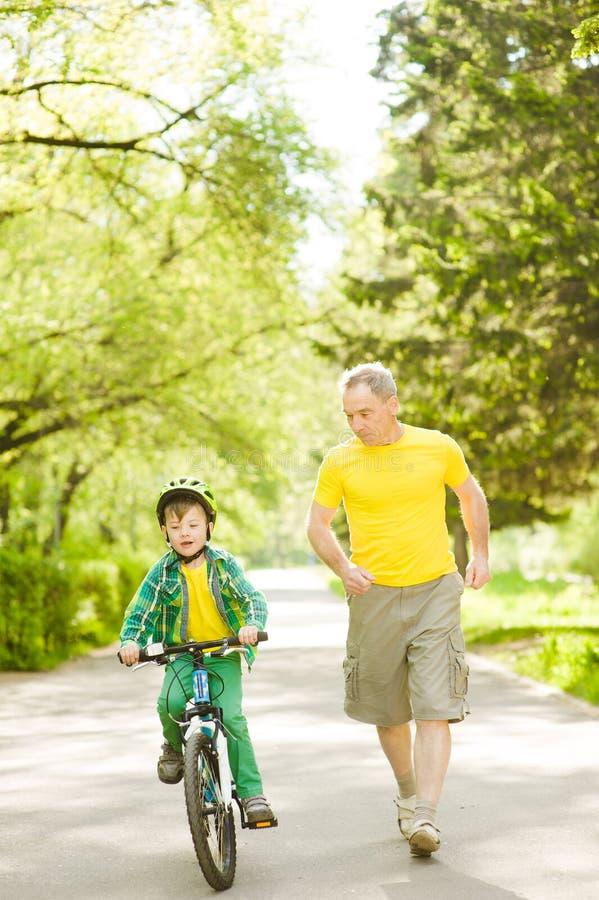 El hombre mayor corre así como su nieto, que monta una bici imagen de archivo libre de regalías