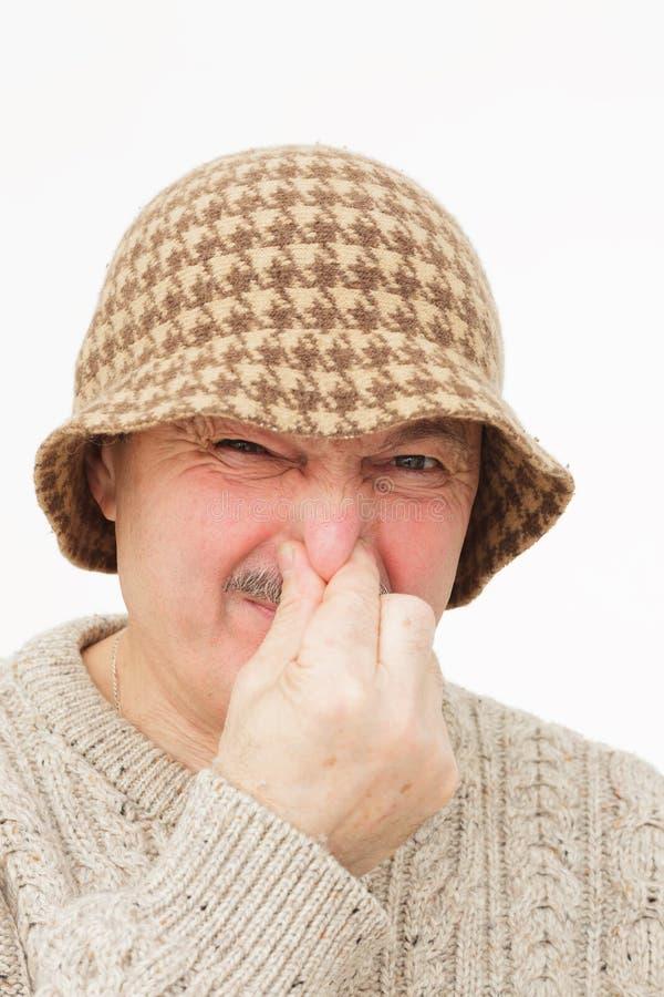 El hombre mayor da los enchufes de la nariz debido a olor desagradable fotografía de archivo libre de regalías