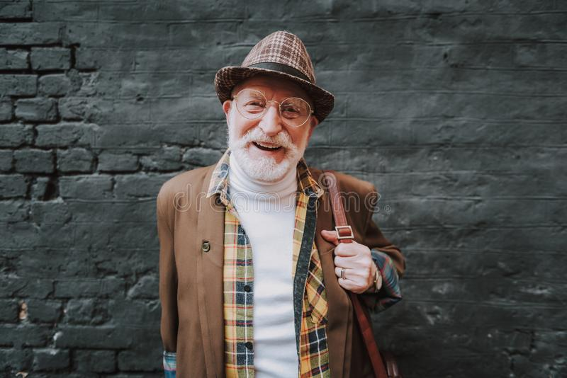 El hombre mayor de moda está sosteniendo una cartera fotos de archivo