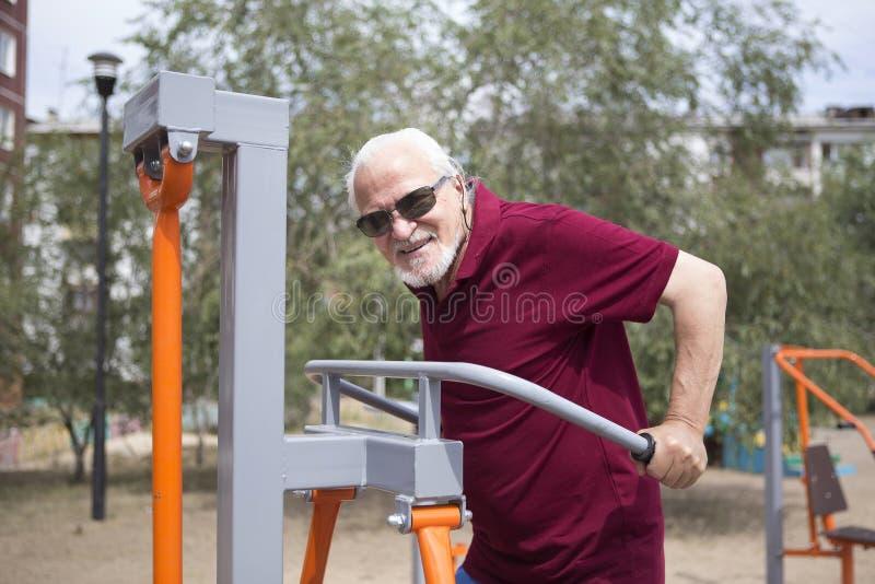 El hombre mayor entrena en el equipo que se divierte en el aire abierto imagen de archivo