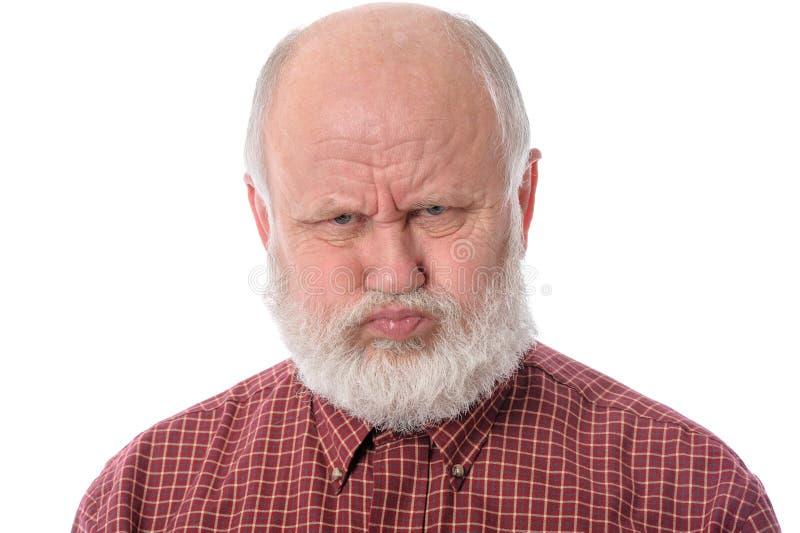 El hombre mayor muestra la expresión facial resentida, aislada en blanco foto de archivo