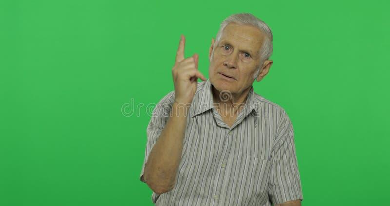 El hombre mayor pelea en alguien Viejo hombre hermoso en el fondo dominante de la croma fotografía de archivo