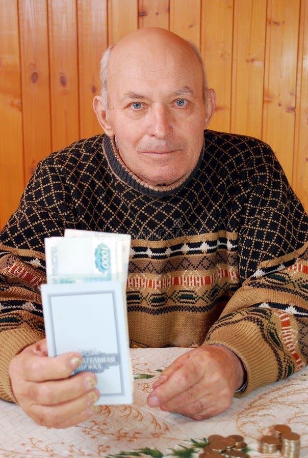 El hombre mayor que se sienta en una tabla lleva a cabo a disposición los ahorros reserva con el dinero invertido en él foto de archivo libre de regalías