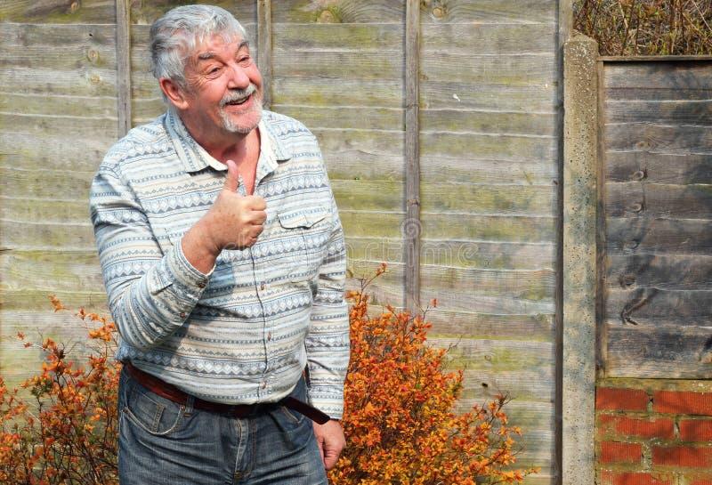 El hombre mayor que sonríe y que da manosea con los dedos encima de muestra. fotografía de archivo